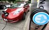 A Nissan Leaf charges at an electric vehicle charging station